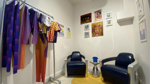 Manon Planche and Emily Eby's pop-up shop with a rack of colourful clothes, 2 chairs and some artwork